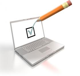 open laptop with screen showing green tick and orange pencil ticking screen